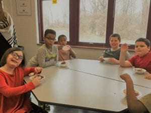 students smile around a table with ice cream at the PBIS ice cream social