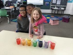 """Photo of students conducting the """"can water walk"""" experiment"""
