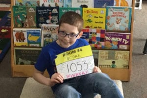 Student posts in front of books with a sign showing Room #4 score 1053 - winner!