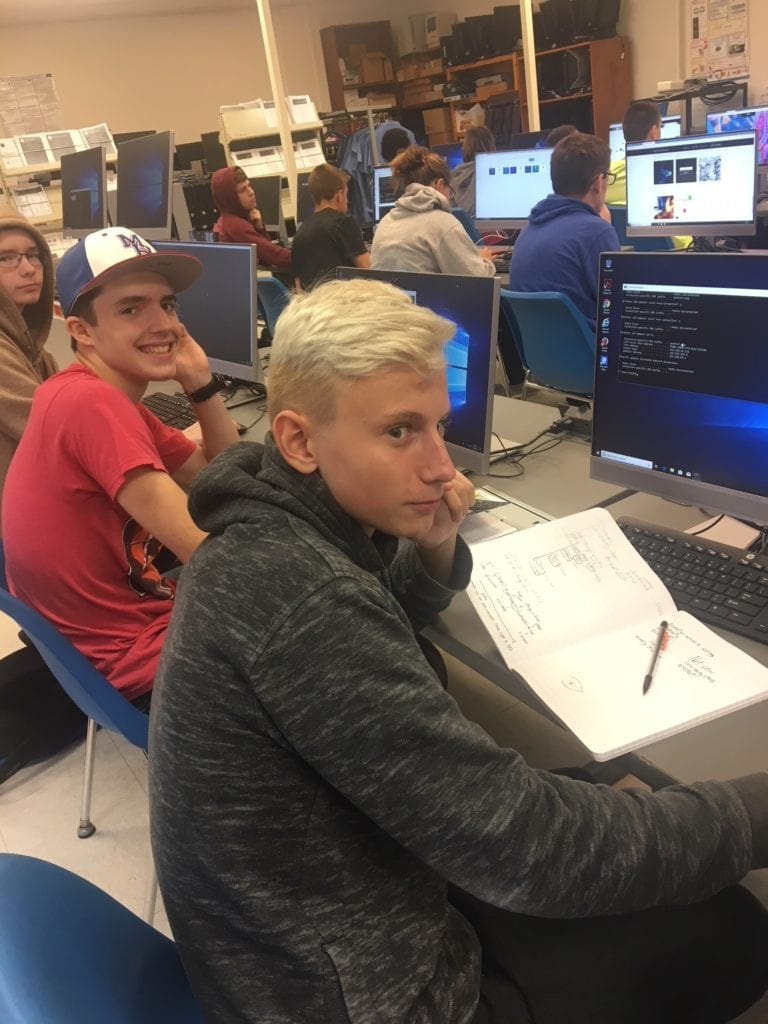 Student Haiden Zinzow at his computer working on code and taking notes.