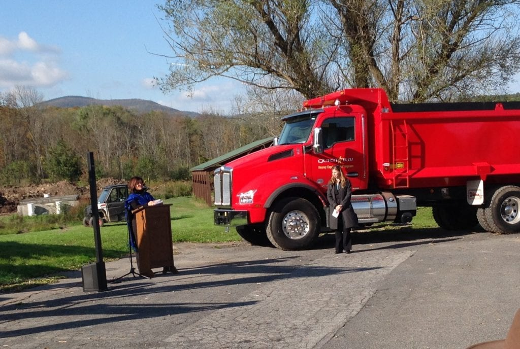 Photo of Dr. Gladys Cruz speaking at a podium next to a red dump truck.