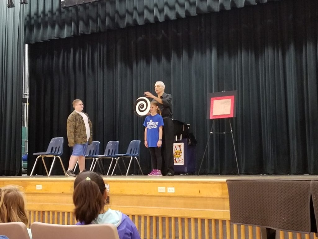 photo of magician on stage with a student.
