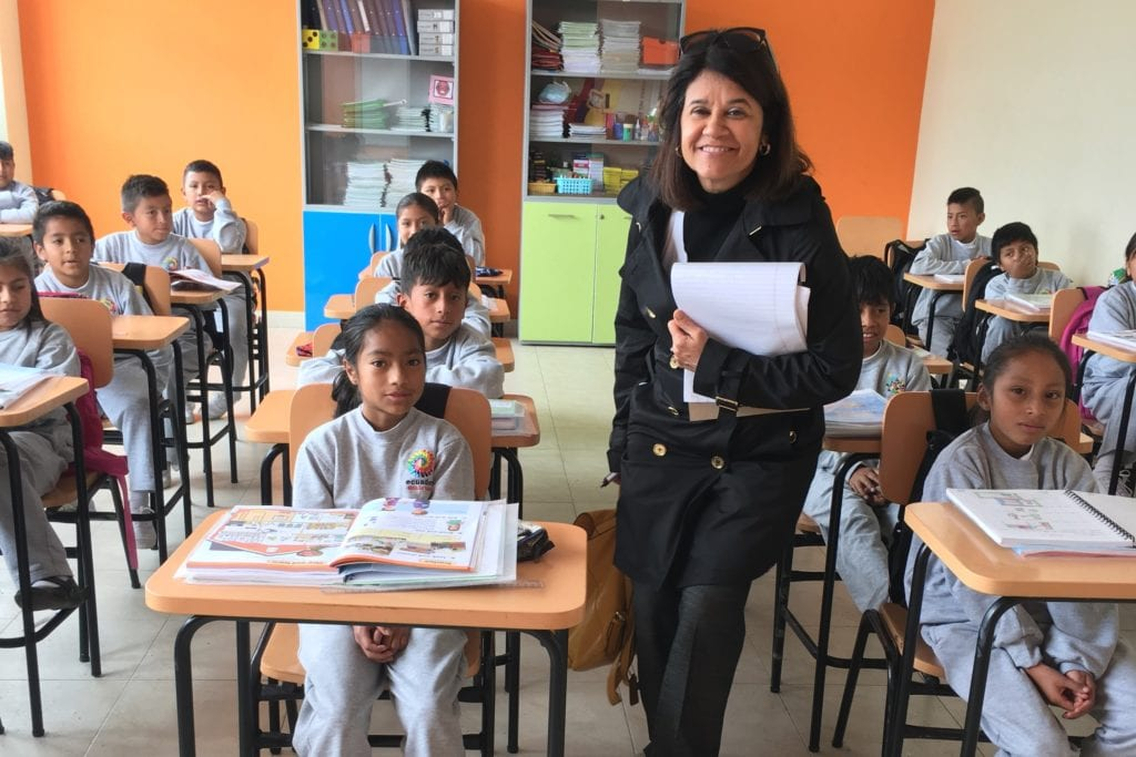 photo of Gladys Cruz in a classroom with students in Ecuador