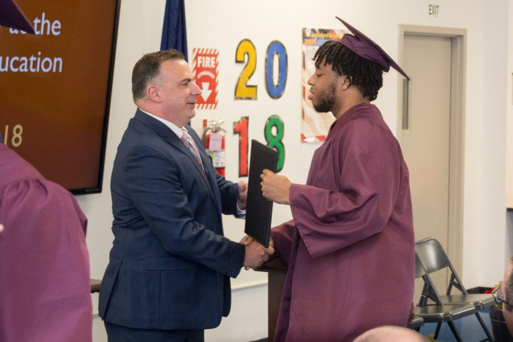 Image of Chris Martel shaking a students hand as he awards a diploma