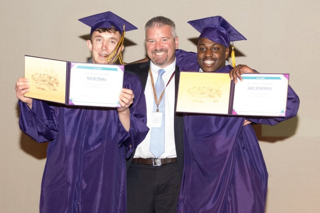 Photo of Andy Pemrick with two graduates holding diplomas