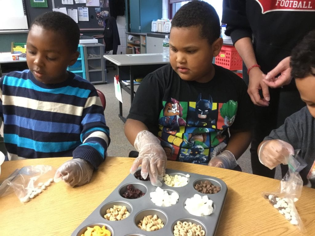 photo of students sorting trail mix in a cupcake tin