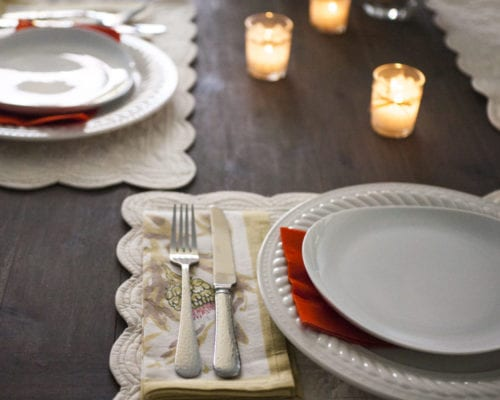 Photo of place settings and candles on a holiday table
