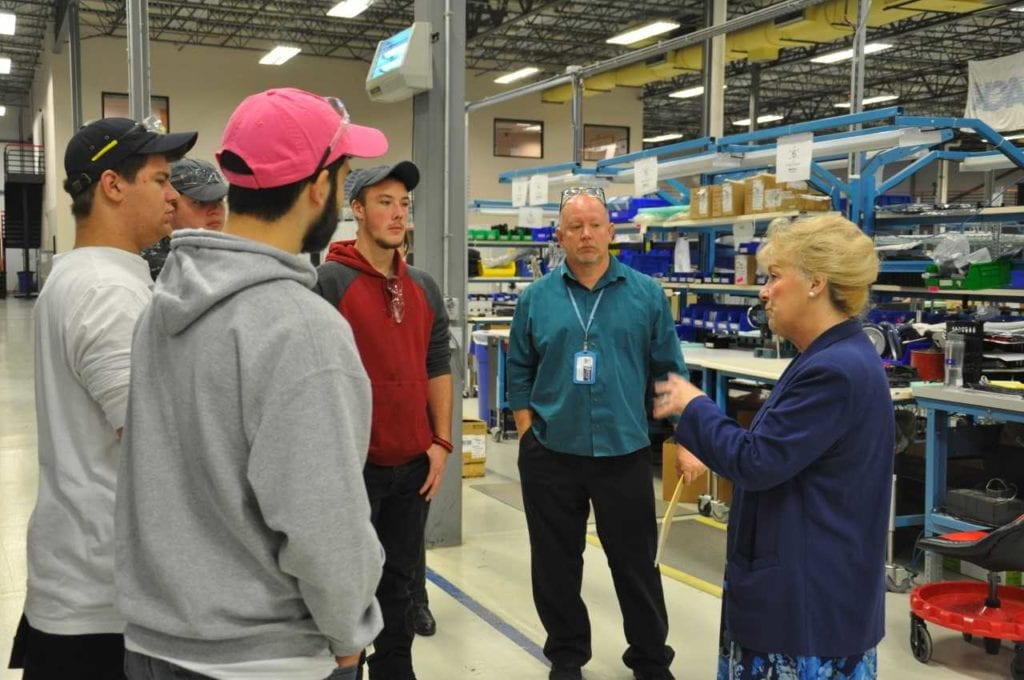 photo of students in a manufacturing facility speaking with professionals