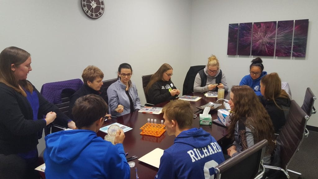students around a conference table study various scientific activities