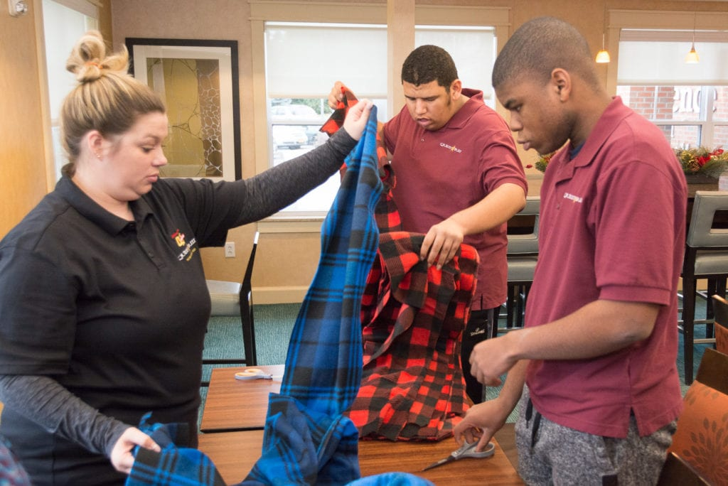 two students and a teacher sort fabric at a table