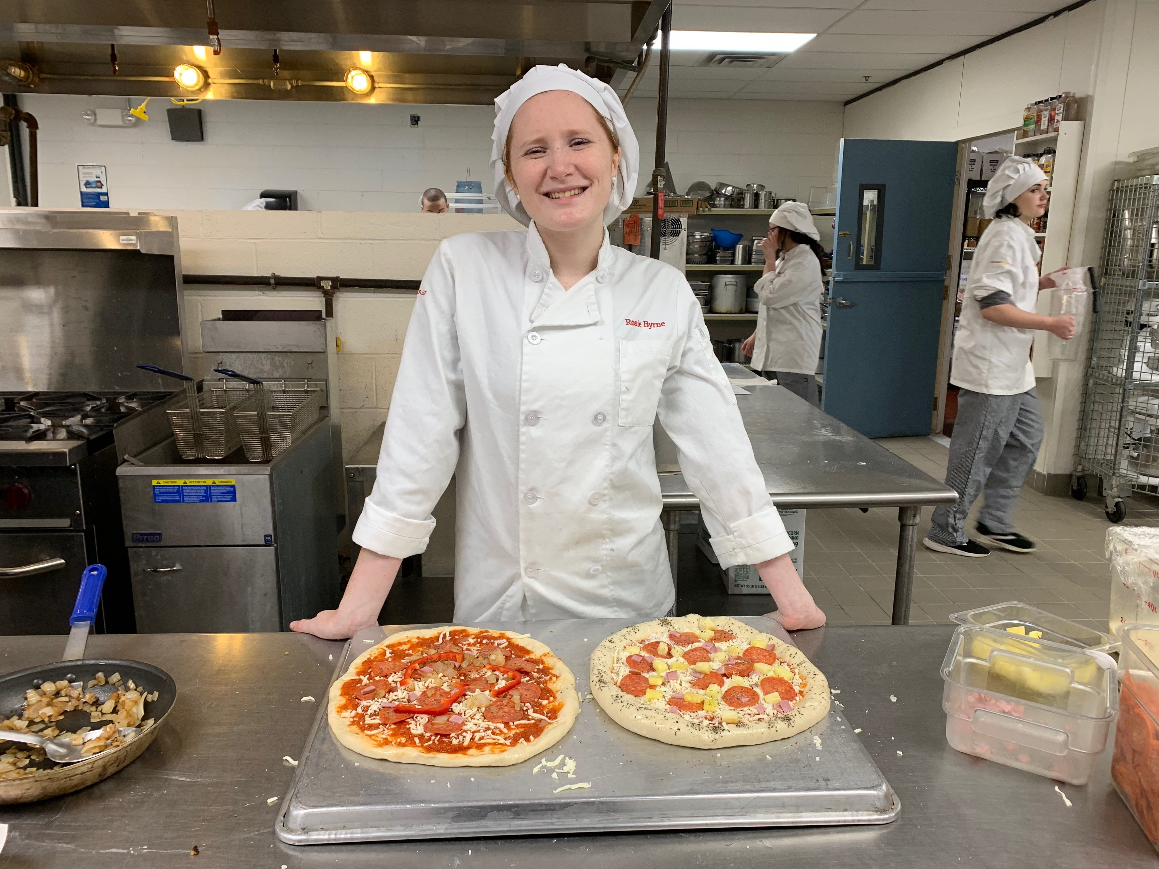 Photo of culinary arts student in kitchen with pizza