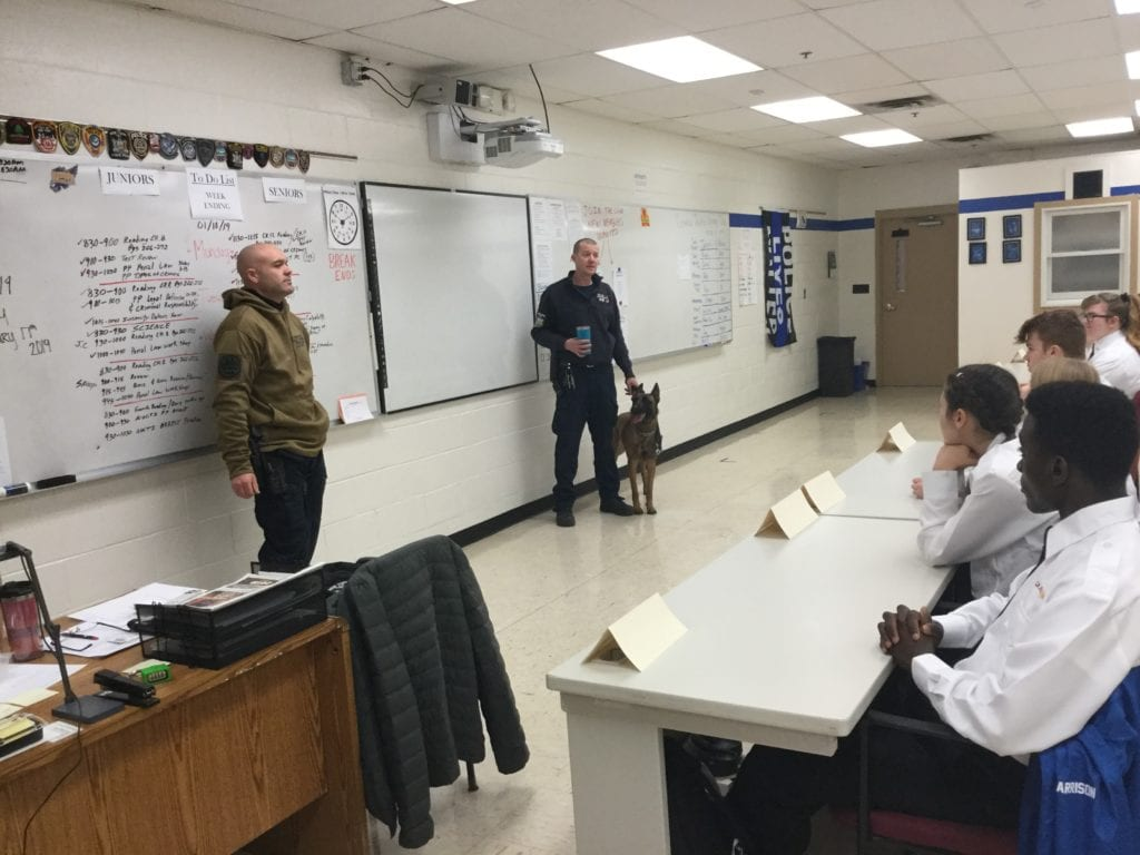 Photo of two new york state police officers with a bomb dog in front of a class.