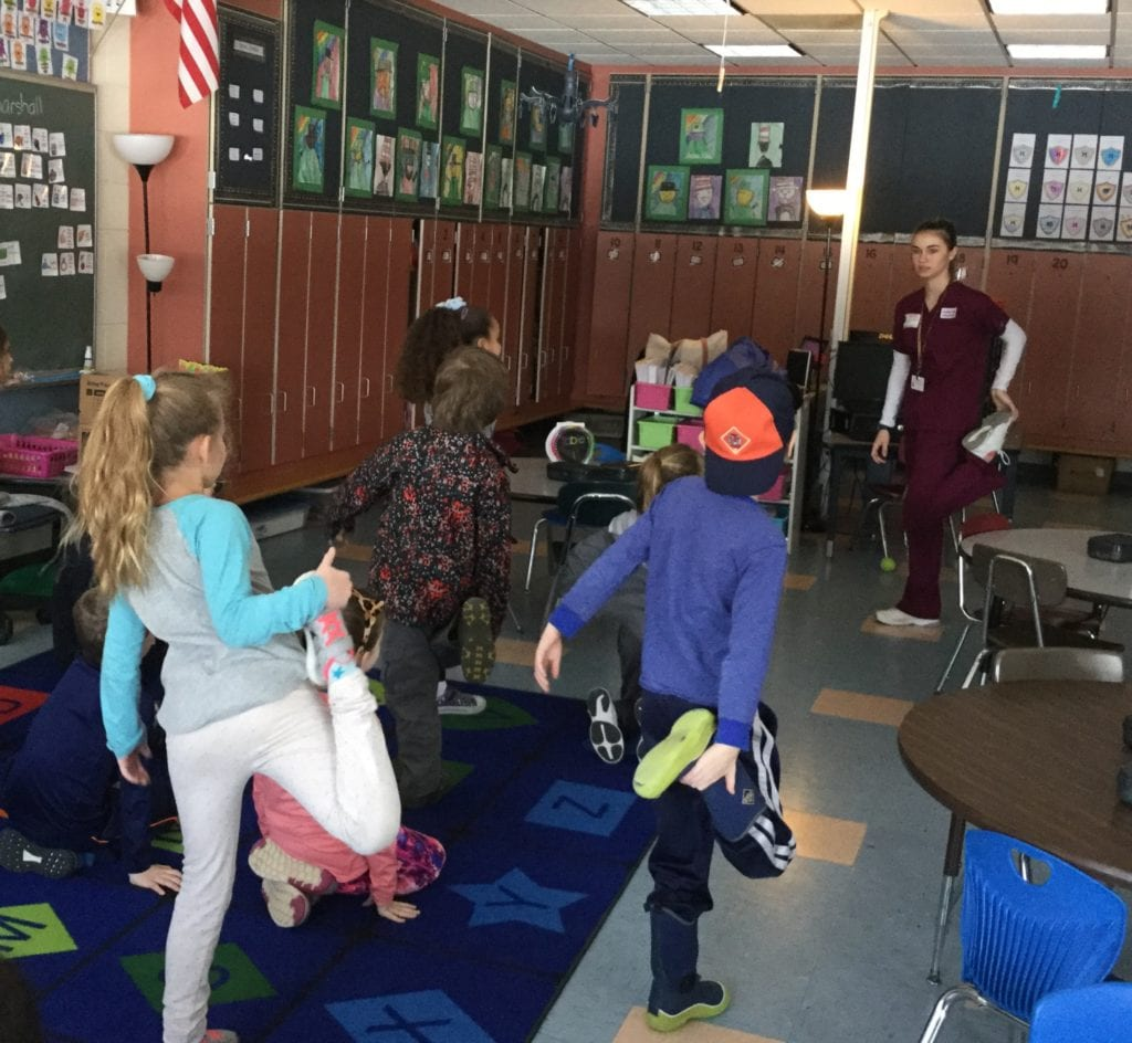 Images of young adult female in a burgandy nursing uniform showing younger students how to hold up their legs.