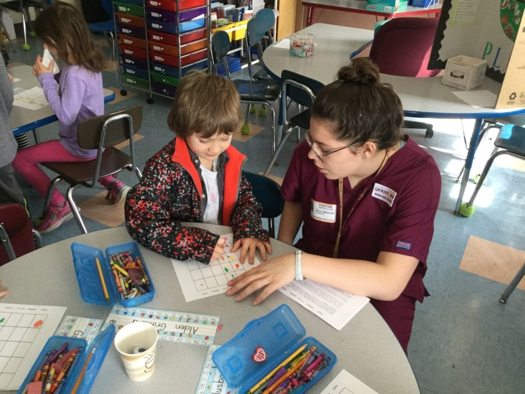 Image of a female student in a burgandy nursing uniform kneeling down to help a young child with a drawing project.