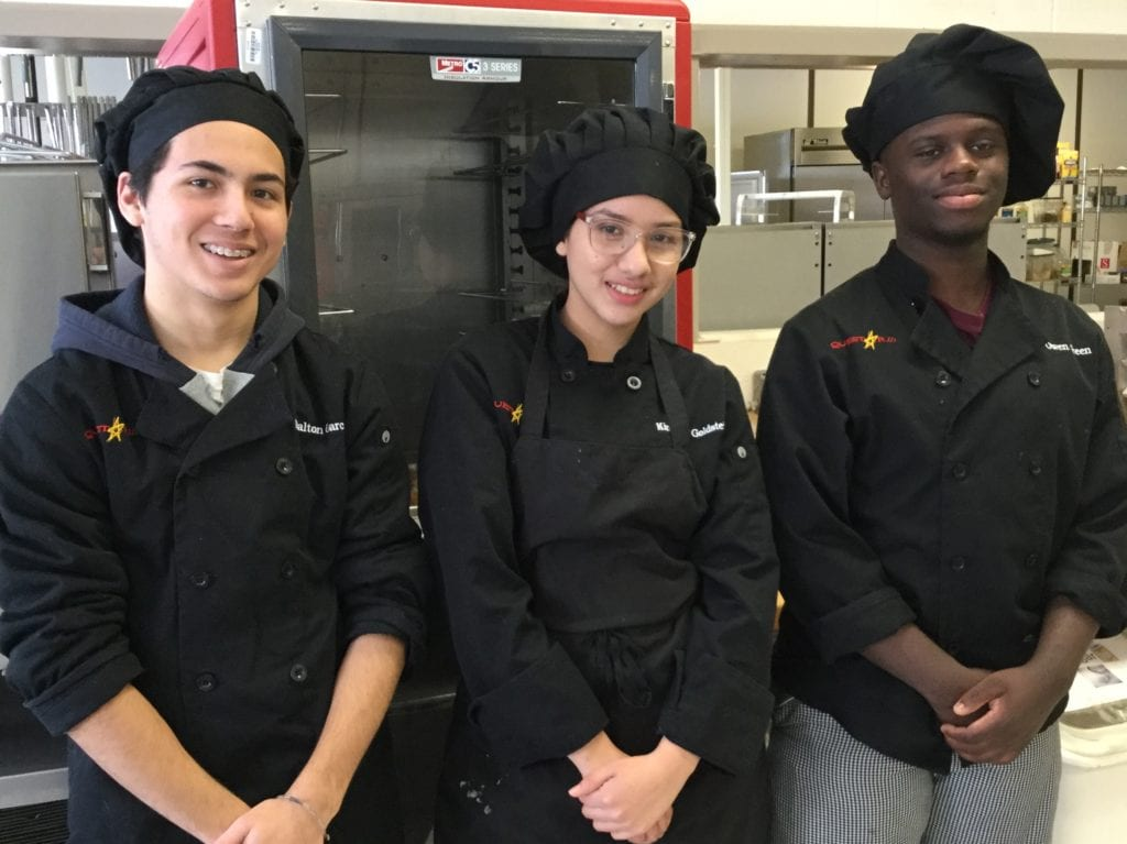 Images of two male students and one female student dressed in Culinary uniforms standing together as a team.