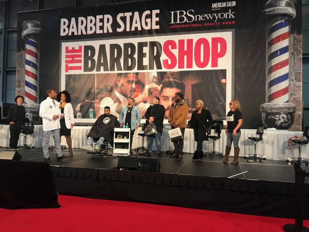 Image of men and women on stage with the words The Barber Shop and two barber poles.