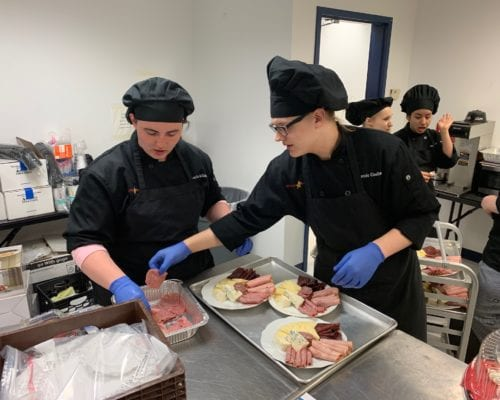 Photo of two culinary arts students preparing trays of appetizers in a kitchen