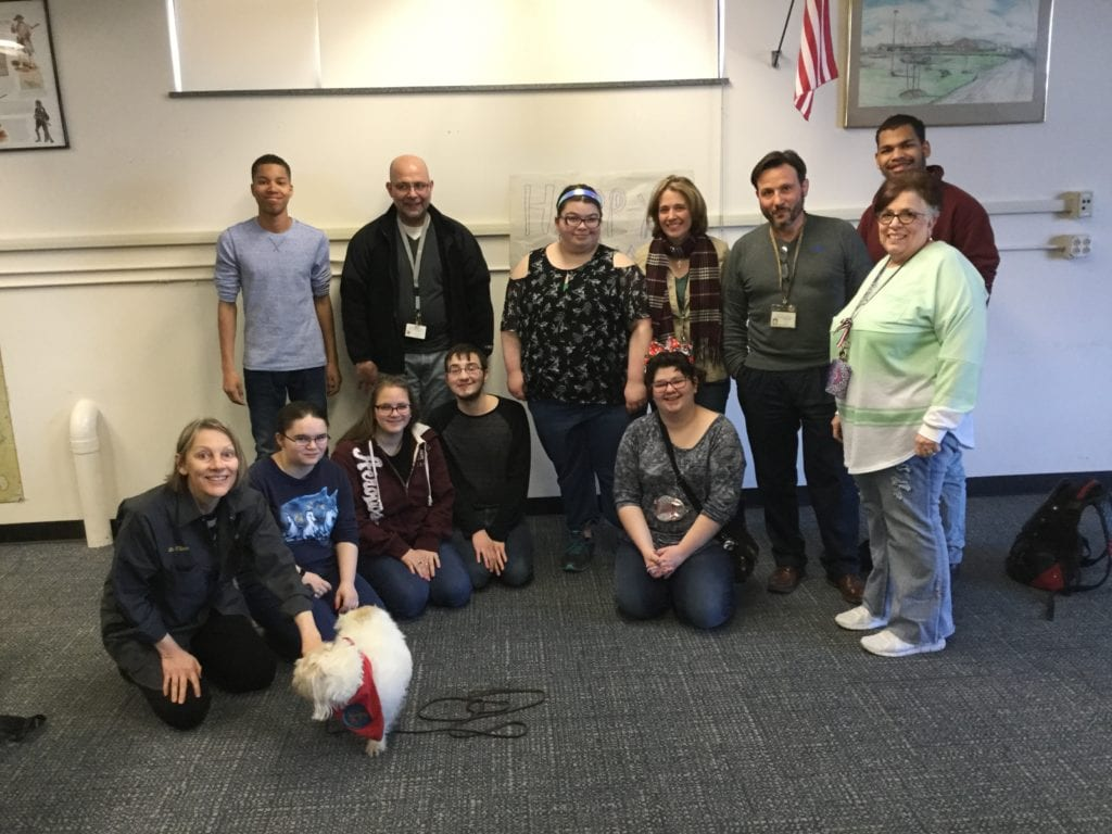group photo of staff and students with a therapy dog