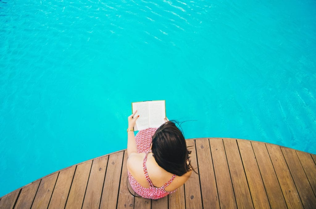 photo of a woman sitting on a wooden dock reading a book by the water