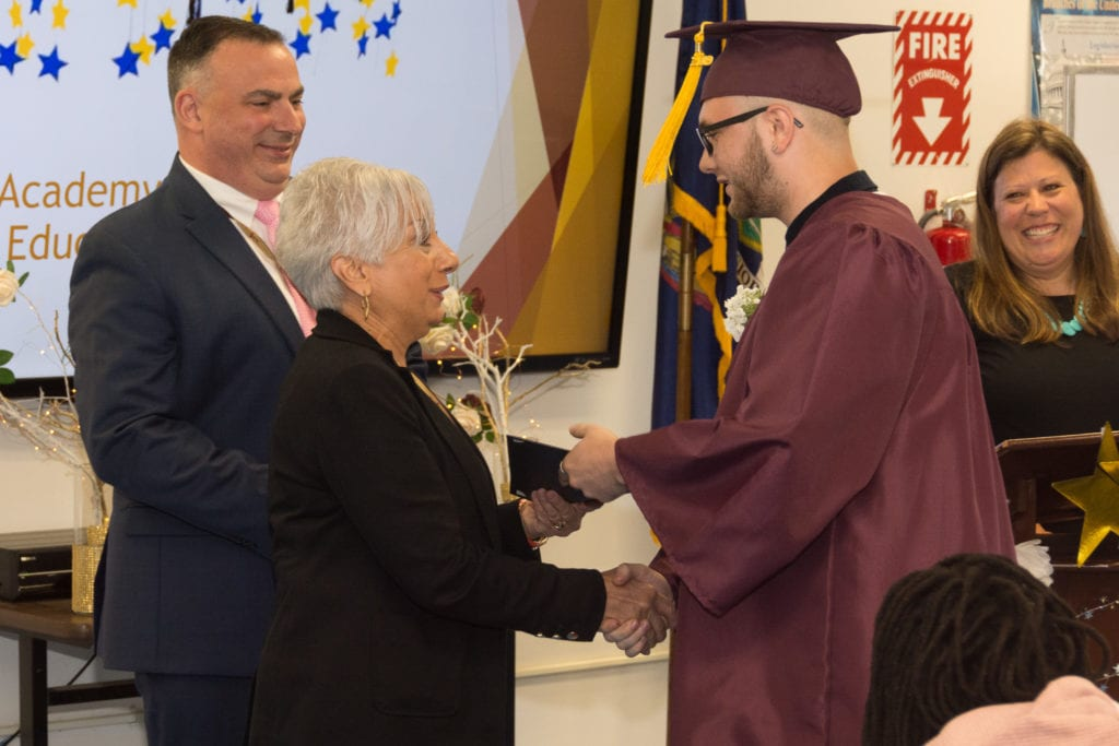 a student receives his diploma and shakes hands with administrators