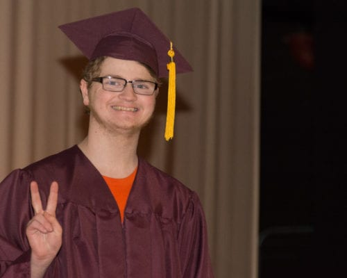 photo of student in maroon cap and gown gives the peace sign