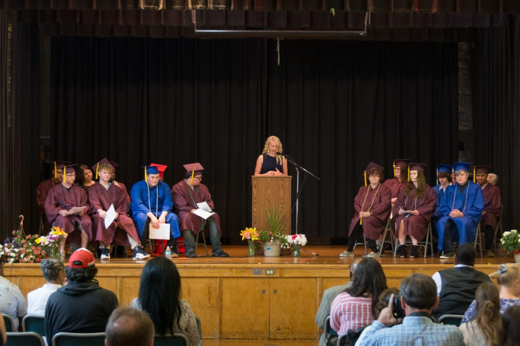 Photo of graduates on stage with a woman speaking at the podium