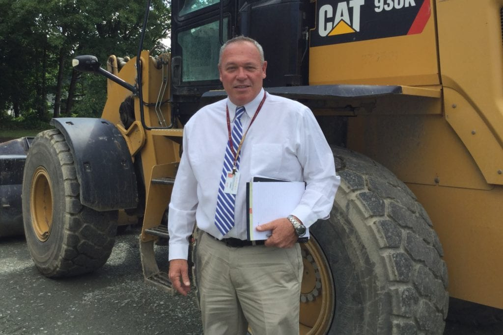 Photo of Joe O'Grady in front of construction equipment