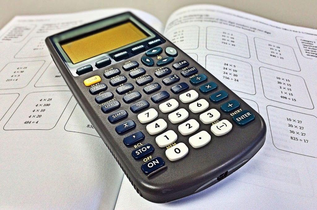 photo of a calculator on top of an open math workbook
