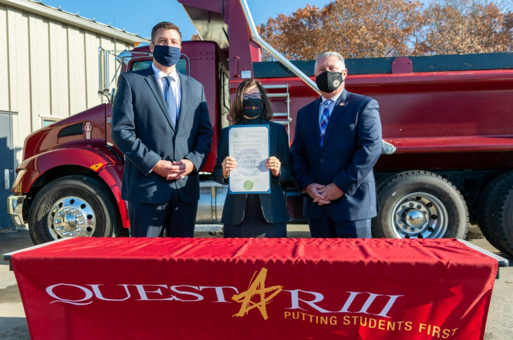 Photo of Assemblyman Ashby, District Superintendent Dr. Gladys I. Cruz and Assemblyman John McDonalds in front of a dump truck